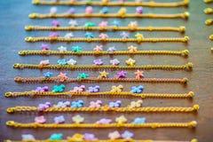 File della catena dorata del braccialetto con i pendenti svegli da vendere nel negozio di gioielli Le catene fatte a mano dorate  Fotografia Stock Libera da Diritti