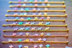 File della catena dorata del braccialetto con i pendenti svegli da vendere nel negozio di gioielli Le catene fatte a mano dorate  Fotografia Stock
