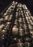 File delle candele brucianti dentro una chiesa immagine stock