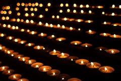 File delle candele nel posto scuro fotografia stock libera da diritti