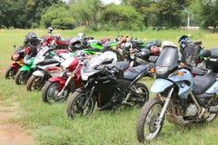 File delle motociclette parcheggiate colourful su erba verde Immagine Stock