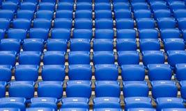 File delle poltrone di plastica blu su una tribuna dello stadio Fotografie Stock Libere da Diritti