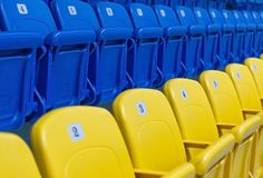File delle sedie blu e gialle sullo stadio immagine stock