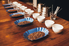 File delle tazze, dei vetri e dei contenitori con i chicchi di caffè Immagini Stock Libere da Diritti