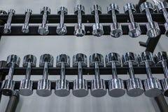 File delle teste di legno del metallo sullo scaffale nella palestra o nel club di sport Attrezzatura di addestramento del peso Immagine Stock