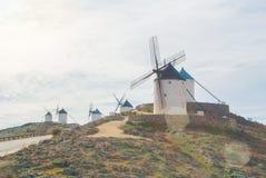 File di vecchi mulini a vento tradizionali bianchi sulla collina vicino a Consueg fotografie stock