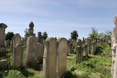 File di vecchie lapidi in un cimitero Fotografie Stock