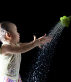 File of face of asian baby playing with water on black backgroun Royalty Free Stock Photos