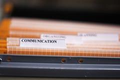 File Folder Labeled Communication. Orange file folders labeled with communication word Royalty Free Stock Images