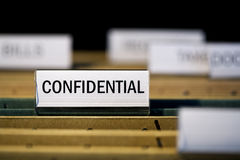 File folder labeled confidential. View inside filing cabinet with brown file folders, green folder with confidential label in focus Royalty Free Stock Photo