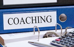 File folder marked coaching. With printed pages, pen and calculator stock images