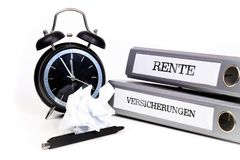 File folders and alarm clock symbolize time pressure. Translatio. N: `Pension` and `Insurance Stock Photography