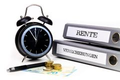File folders and alarm clock symbolize time pressure. Translatio. N: `Pension` and `Insurance Stock Photos