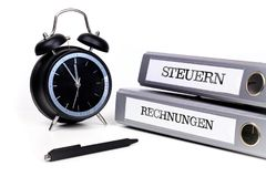 File folders and alarm clock symbolize time pressure. Translatio. N: `Taxes` and `Bills Stock Images