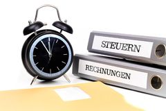 File folders and alarm clock symbolize time pressure. Translatio. N: `Taxes` and `Bills Stock Photography