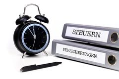 File folders and alarm clock symbolize time pressure. Translatio. N: `Taxes` and `Insurance Stock Images