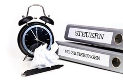 File folders and alarm clock symbolize time pressure. Translatio. N: `Taxes` and `Insurance Stock Photography