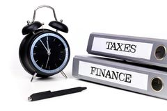 File folders and alarm clock symbolize time pressure while worki. Ng on taxes and finance Royalty Free Stock Photos