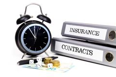 File folders and alarm clock symbolize time pressure while worki. Ng on contracts and insurance Stock Photo