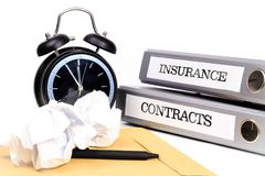 File folders and alarm clock symbolize time pressure while worki. Ng on contracts and insurance Stock Image