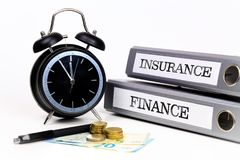 File folders and alarm clock symbolize time pressure while worki. Ng on finance and insurance Stock Images