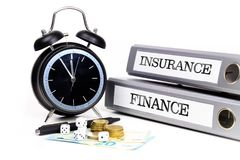 File folders and alarm clock symbolize time pressure while worki. Ng on finance and insurance Royalty Free Stock Photos