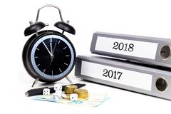 File folders and alarm clock symbolize time pressure while working on the plans for 2018 stock images