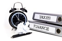 File folders and alarm clock symbolize time pressure while worki. Ng on taxes and finance Royalty Free Stock Image