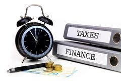File folders and alarm clock symbolize time pressure while worki. Ng on taxes and finance Royalty Free Stock Photo