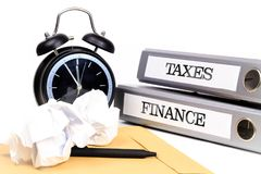 File folders and alarm clock symbolize time pressure while worki. Ng on taxes and finance Stock Photos