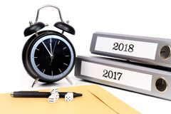 File folders and alarm clock symbolize time pressure while worki. Ng on the plans for 2018 Royalty Free Stock Photo