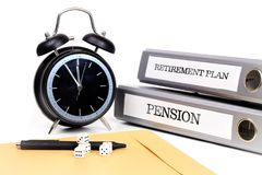 File folders and alarm clock symbolize time pressure while worki. Ng on retirement plan and pension Stock Photos