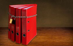 File folders with chain and lock on wooden table royalty free stock images