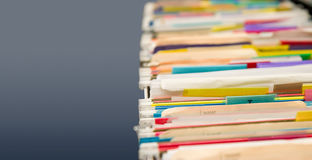 File folders full of data. Multi colored file folders showing signs of heavy use with gray copy space Stock Image