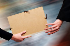 File Relay. Two persons exchanging a file as a relay baton. Motion blur at the background royalty free stock image