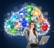 File storage - Girl  using laptop. Multimedia storage -  girl  with laptop looking at clouds  with multimedia icons Stock Image