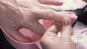 A file to process a fingernail and to move away a cuticle. Of a nail of the elderly woman stock footage