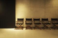 Fileira da cadeira do ` s do diretor no fundo cinzento do cimento no estúdio imagens de stock