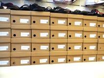 Fileira da caixa de sapatas e das sapatas empilhadas na loja fotos de stock