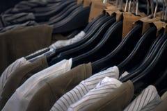 Fileira da camisa colorida diferente no gancho, na roupa em ganchos em uma loja ou na sala de exposições Imagem de Stock
