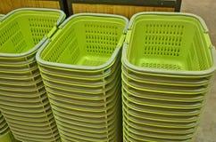 A fileira da cesta verde empilha em uma loja Imagem de Stock
