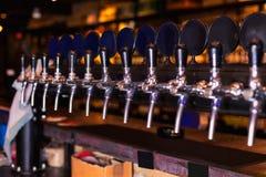 Fileira da torneira da cerveja no contador da barra imagens de stock