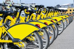 Fileira das bicicletas estacionadas Fileira de bicicletas coloridas estacionadas Bicicletas amarelas alugado O teste padrão do vi Foto de Stock