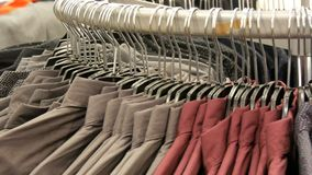 Fileira das camisas elegantes dos vários homens em um gancho enorme na loja de roupa dos homens no shopping filme
