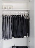 Fileira das camisas pretas e cinzentas que penduram no gancho de revestimento Imagens de Stock