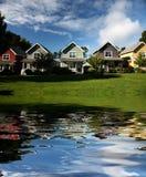 Fileira das casas que refletem na água imagem de stock