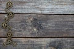 Fileira das engrenagens em um fundo de madeira imagem de stock
