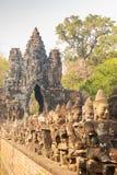 Fileira das est?tuas que conduzem a uma maneira de passagem no local monumental do patrim?nio mundial de cambodia do angkor da po foto de stock