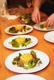 A fileira das placas com salada serviu na tabela Fotografia de Stock Royalty Free