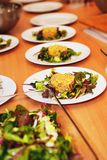 A fileira das placas com salada serviu na tabela Foto de Stock